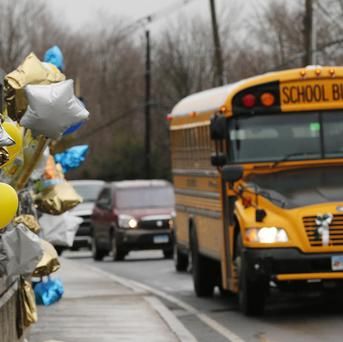 A school bus rolls toward a memorial in Newtown, Connecticut for victims of the Sandy Hook Elementary School shooting (AP/Charles Krupa)