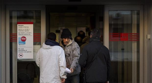 A man leaves an unemployment office in Madrid (AP)
