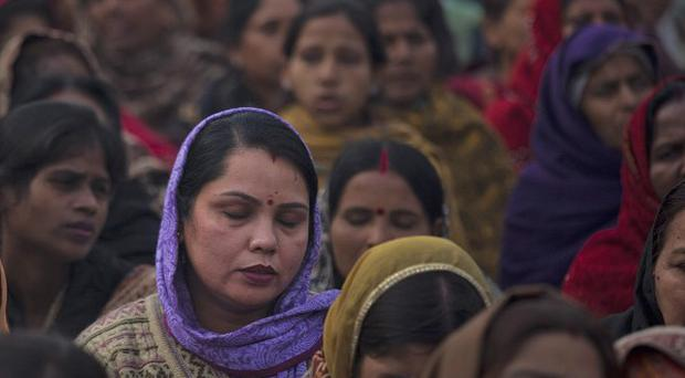 Indian women offer prayers for a gang rape victim at Mahatma Gandhi memorial in New Delhi, India (AP)