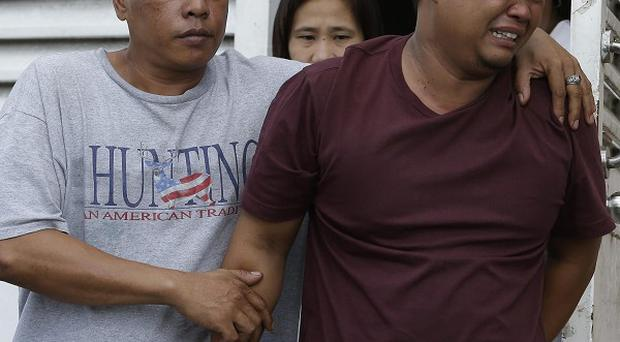 Edmund De Vera cries after viewing the body of his five-year-old son John-John, who was shot in Kwait (AP)