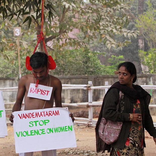 Protesters wearing placards pretend to be rapists wearing a hangman's noose in Bhubaneswar, India (AP)