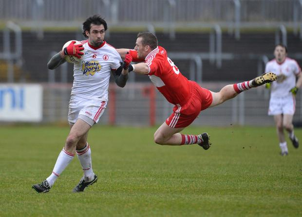 Tyrone's Joe McMahon wrestles with Derry's Paddy Bradley