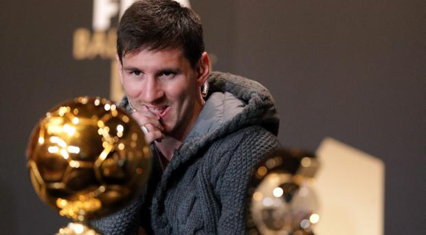 ZURICH, SWITZERLAND - JANUARY 07: Lionel Messi of Barcelona watches Ballon d'Or trophy during the Press Conference with nominees for World Player of the Year and World Coach of the Year for Men's Football on January 7, 2013 at Congress House in Zurich, Switzerland. (Photo by Christof Koepsel/Getty Images)
