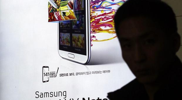 A man holds his mobile phone near an ad for Samsung's Galaxy Note II (AP)
