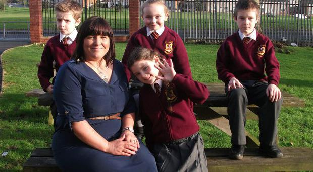 Claire Robinson, principal of St Luke's Primary School in Belfast, with pupils Caithlin McCorley, Caoimhe Doherty, Connell Toner and Liam McIlwaine