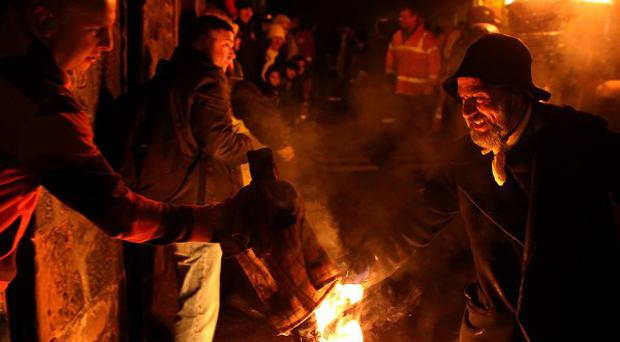 A member of the Clavie Crew hands a piece of the burning clavie to a member of the public