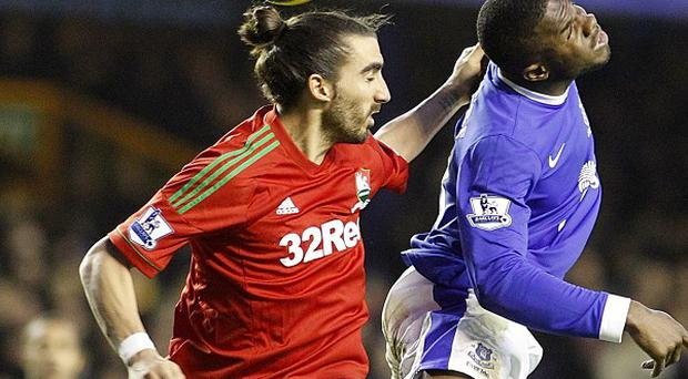 Swansea City's Chico, left, and Everton's Victor Anichebe challenge for the ball