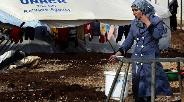 A Syrian refugee fills a bucket with water at a camp near the Syrian border in Jordan (AP)