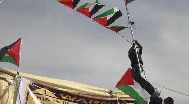 Activists place Palestinian flags in the new 'outpost ' of Bab Al Shams (Gate of the Sun) in an area known as E1, near Jerusalem (AP)