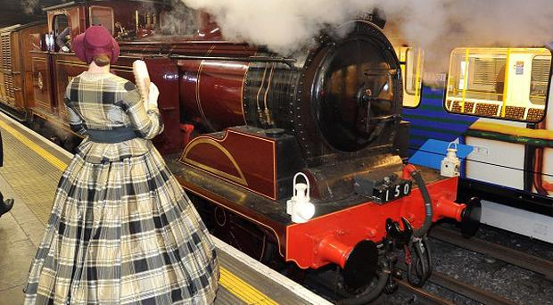 A steam train arrives at Moorgate underground station in the City of London, to celebrate the 150th anniversary of the Tube