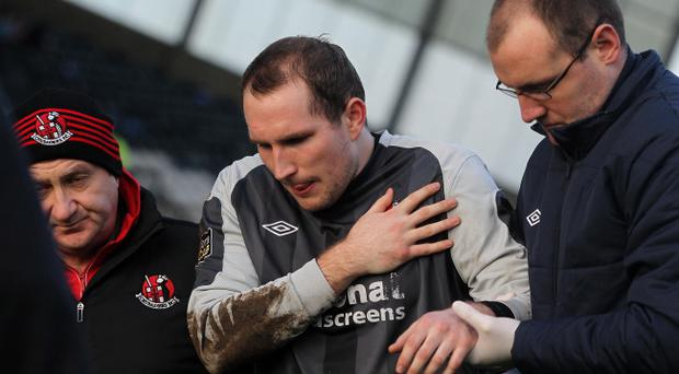 Sean O'Neill is helped from the field after dislocating his shoulder