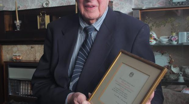 John Gordon with his bravery medal for helping as a fireman at Nutts Corner air crash 60 years ago