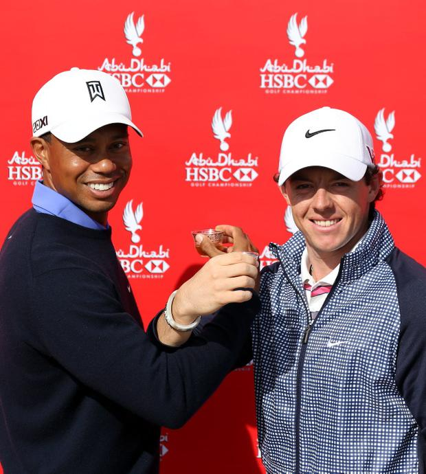 ABU DHABI, UNITED ARAB EMIRATES - JANUARY 15: Tiger Woods of the USA (L) and Rory McIlroy of Northern Ireland interlock arms whilst drinking coffee during a photocall prior to the start of The Abu Dhabi HSBC Golf Championship at the Abu Dhabi Golf Club on January 15, 2013 in Abu Dhabi, United Arab Emirates. (Photo by Ross Kinnaird/Getty Images)