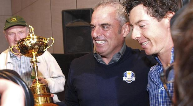 Rory McIlroy, right, congratulates Paul McGinley, holding the Ryder Cup, after he was nominated as the Captain for the 2014 European Ryder Cup Team following a meeting of the Tournament Committee of the European Tour in Abu Dhabi