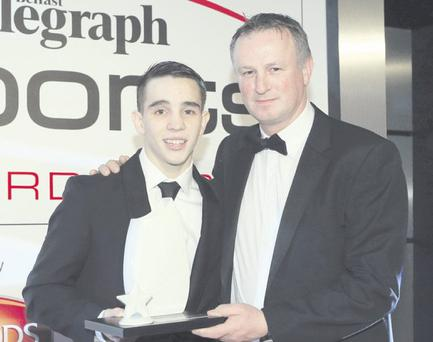 Michael Conlan collects his award from Northern Ireland football manager Michael O'Neill