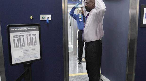 Volunteers pass through the first full body scanner at O'Hare International Airport in Chicago (AP/M Spencer Green)