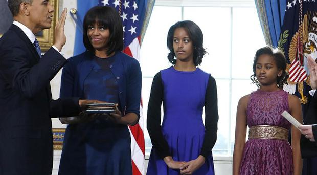 US President Barack Obama is sworn in at the White House alongside his family (AP)