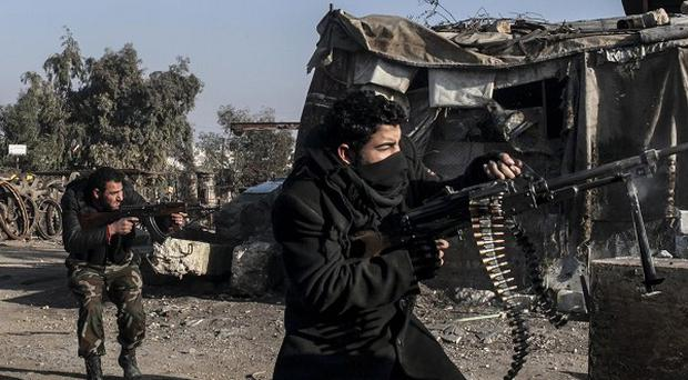 Free Syrian Army fighters fire their weapons during heavy clashes with government forces in Aleppo (AP)