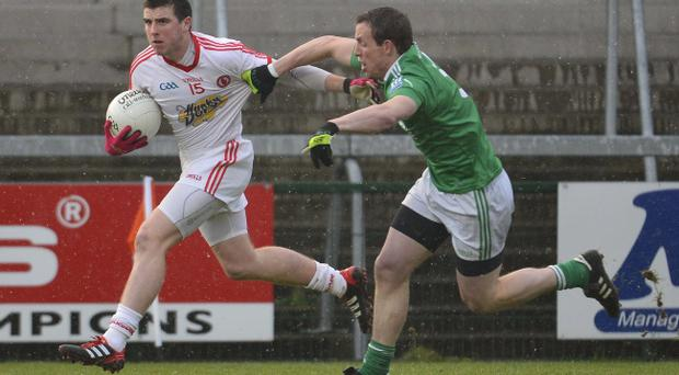 Tyrone's Conor McAliskey is|hauled back by Fermanagh's Shane Lyons