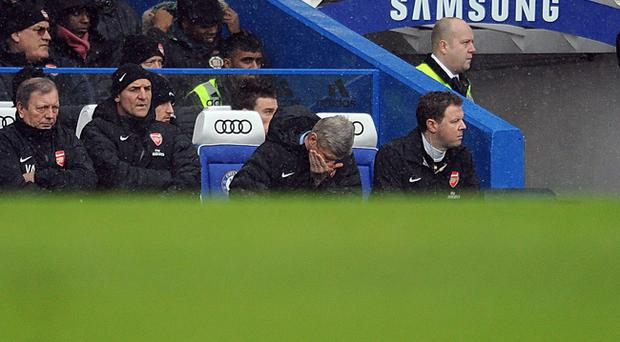 Arsenal's manager Arsene Wenger with his head in his hands on the touchline during the Barclays Premier League match at Stamford Bridge, London. PRESS ASSOCIATION Photo. Picture date: Sunday January 20, 2013. See PA story SOCCER Chelsea. Photo credit should read: Andrew Matthews/PA Wire. RESTRICTIONS: Editorial use only. Maximum 45 images during a match. No video emulation or promotion as 'live'. No use in games, competitions, merchandise, betting or single club/player services. No use with unofficial audio, video, data, fixtures or club/league logos.