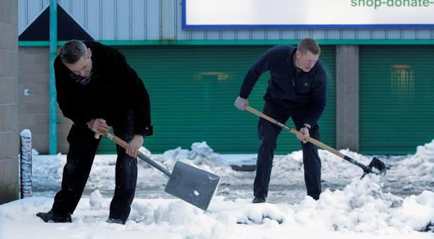 People clear the snow from their work the morning after heavy snowfall in Lisburn.