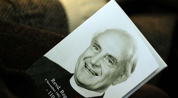 A mourner holds an order of service at the funeral service for Britain's oldest man, Reg Dean