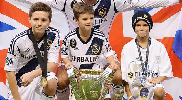 David Beckham poses with his sons (left to right) Brooklyn, Cruz and Romeo