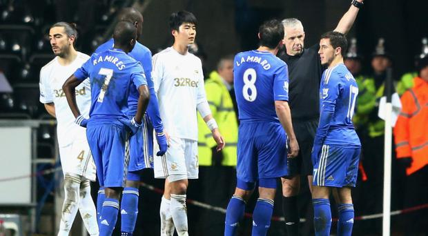 SWANSEA, WALES - JANUARY 23: Eden Hazard of Chelsea (R) is sent off by referee Chris Foy after kicking a ball boy during the Capital One Cup Semi-Final Second Leg match between Swansea City and Chelsea at Liberty Stadium on January 23, 2013 in Swansea, Wales. (Photo by Michael Steele/Getty Images)