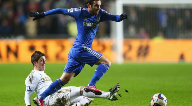 SWANSEA, WALES - JANUARY 23: Juan Mata of Chelsea is challenged by Pablo Hernandez of Swansea City during the Capital One Cup Semi-Final Second Leg match between Swansea City and Chelsea at Liberty Stadium on January 23, 2013 in Swansea, Wales. (Photo by Michael Steele/Getty Images)