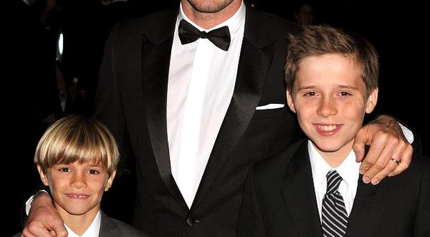 Brooklyn Beckham with dad David and brother Romeo