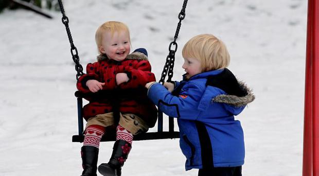 Liam Law (3) pushes his sister Kate on the swing at Shaw's Bridge, Belfast