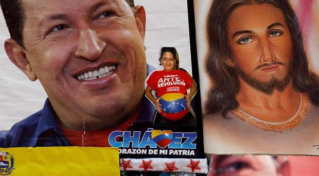 A photograph of Venezuela's President Hugo Chavez, alongside one of Jesus Christ, held by a Chavez supporter at a rally in Caracas (AP)
