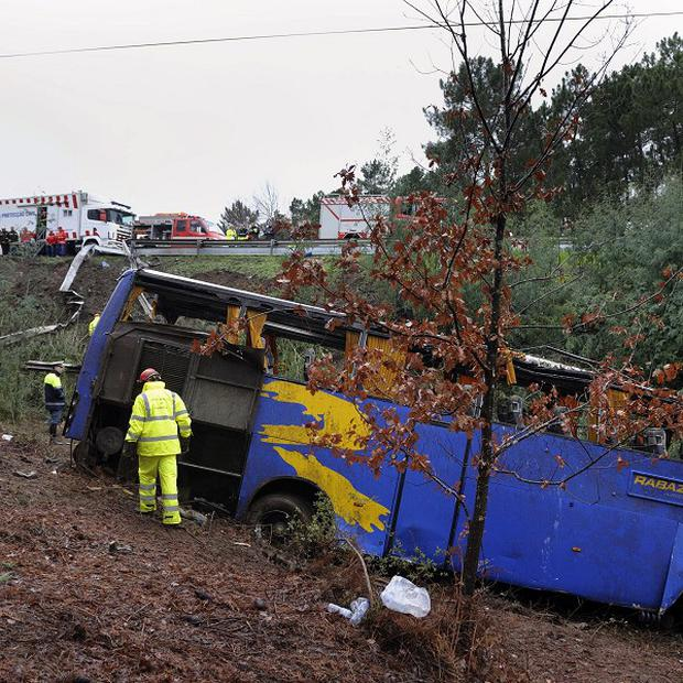 Portuguese firefighters work around the wreckage of a bus which ran off the road and crashed into a ravine, killing 10 people (AP)