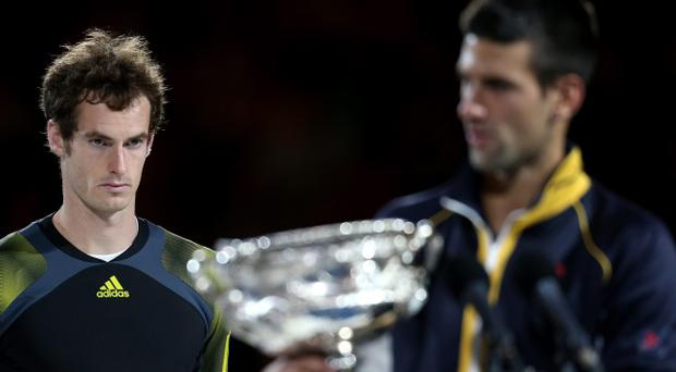MELBOURNE, AUSTRALIA - JANUARY 27: Andy Murray of Great Britain (L) watches Novak Djokovic of Serbia hold the Norman Brookes Challenge Cup after Djokovic won their men's final match during day fourteen of the 2013 Australian Open at Melbourne Park on January 27, 2013 in Melbourne, Australia. (Photo by Scott Barbour/Getty Images)
