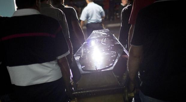 Relatives and friends carry the coffin of a victim in Santa Maria city (AP)