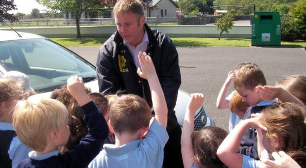 Murdered Garda Adrian Donohoe talks to pupils at Bellurgan National School as part of his work in the community
