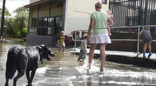 A mother and her children walk through floodwaters caused by torrential rains in Lismore, New South Wales (AP/NSW State Emergency Service )