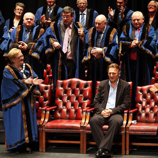 Liam Neeson is applauded by councillors after accepting the freedom of Ballymena at the town hall