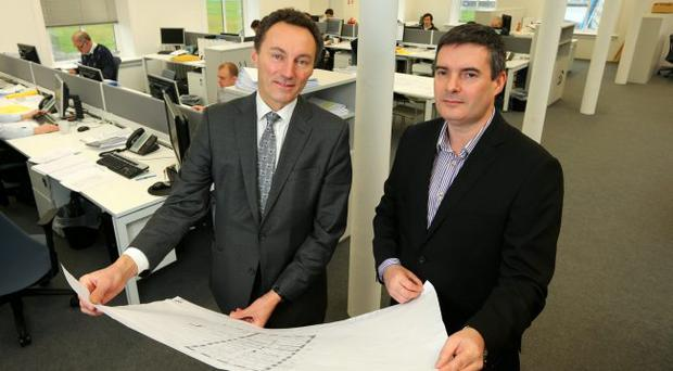 David Gavaghan (left), CEO of Titanic Quarter Ltd, and Paul Crowe, managing director of Todd Architects and Planners, look over the original plans for Titanic House, to which the architectural practice has relocated its Belfast offices