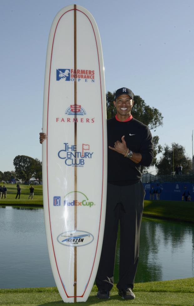 LA JOLLA, CA - JANUARY 28: Tiger Woods celebrates his -14 under win with the winner's surfboard during the Final Round at the Farmers Insurance Open at Torrey Pines Golf Course on January 28, 2013 in La Jolla, California. (Photo by Donald Miralle/Getty Images)