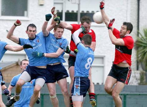 UCC and UUJ players contest a dropping ball