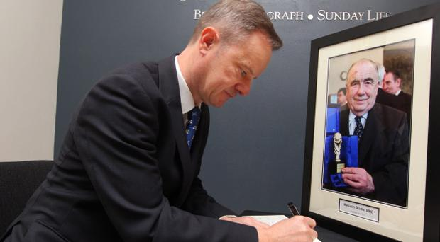 Mike Gilson, editor of the Belfast Telegraph, signs the book of condolences for Malcolm Brodie in the Belfast Telegraph's reception area