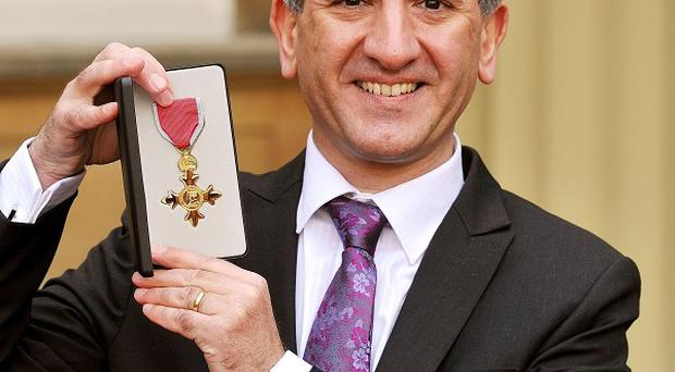 Armando Iannucci holds his Order of the British Empire medal after it was presented to him by the Prince of Wales at Buckingham Palace