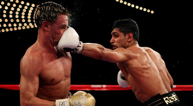 Paulie Malignaggi takes a blow from Amir Khan during their WBA light welterweight title fight at Madison Square Garden