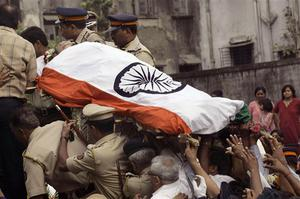 The body of Hemant Karkare, the chief of Mumbai's Anti-Terrorist Squad, who was killed by gunmen, is seen covered in National flag during the funeral procession in Mumbai, India, Saturday, Nov. 29, 2008. Indian commandos killed the last remaining gunmen holed up at a luxury Mumbai hotel Saturday, ending a 60-hour rampage through India's financial capital by suspected Islamic militants that killed people and rocked the nation. (AP Photo/Rajanish Kakade)