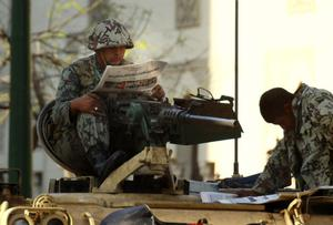 Egyptian army soldiers read newspapers as they sit atop their armored vehicles in Cairo, Egypt, Sunday, Jan. 30, 2011. With the police having disappeared from the streets, residents reported gangs of youths, some on motorbikes, roaming the streets, looting supermarkets, shopping malls and stores. Some of the gangs made it to affluent residential areas in the suburbs, breaking into luxury homes and apartments. The crackle of gunfire could be heard in the city center as well as outlying districts. (AP Photo/Amr Nabil)
