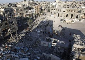 Palestinians inspect the rubble of a destroyed house after an Israeli airstrike next to a mosque, back, in the Jabaliya refugee camp, northern Gaza Strip, Sunday, Nov. 18, 2012. The Israeli military widened its range of targets in the Gaza Strip on Sunday to include the media operations of the Palestinian territory's Hamas rulers, sending its aircraft to attack two buildings used by both Hamas and foreign media outlets. (AP Photo/Hatem Moussa)