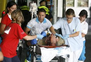 Medical personel tend an injured passenger in Madrid's Barajas airport after a Spanair airliner bound for the Canary Islands swerved off the runway while taking off from the airport, Madrid, Spain, Wednesday, Aug. 20, 2008. Local media are reporting that at least 20 people died in the accident and 57 were injured. (AP Photo/EFE, Juan Carlos Hidalgo) ** NO SALES, LATIN AMERICA, CARIBBEAN AND SPAIN OUT **