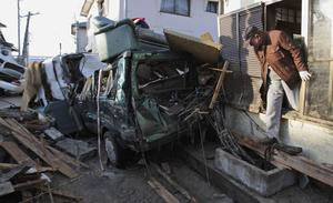 A man climbs out the window of his heavily damaged home Monday, March 14, 2011, in Yotsukura, Japan, three days after a giant quake and tsunami struck the country's northeastern coast. (AP Photo/Gregory Bull)