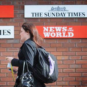 A member of staff walks by the main entrance to News International Newspapers Ltd in Wapping, east London